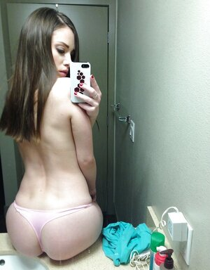 Sexy kitten takes selfies as she strips off clothes and flashes snatch