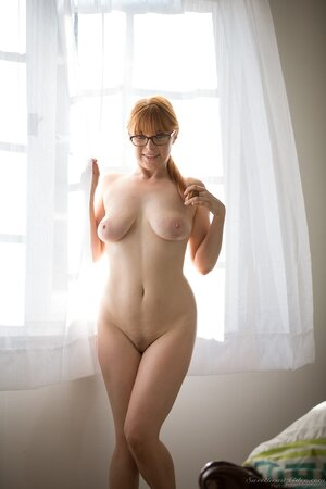 Horny redhead needs more than just jumping on bed so she gets naked before window